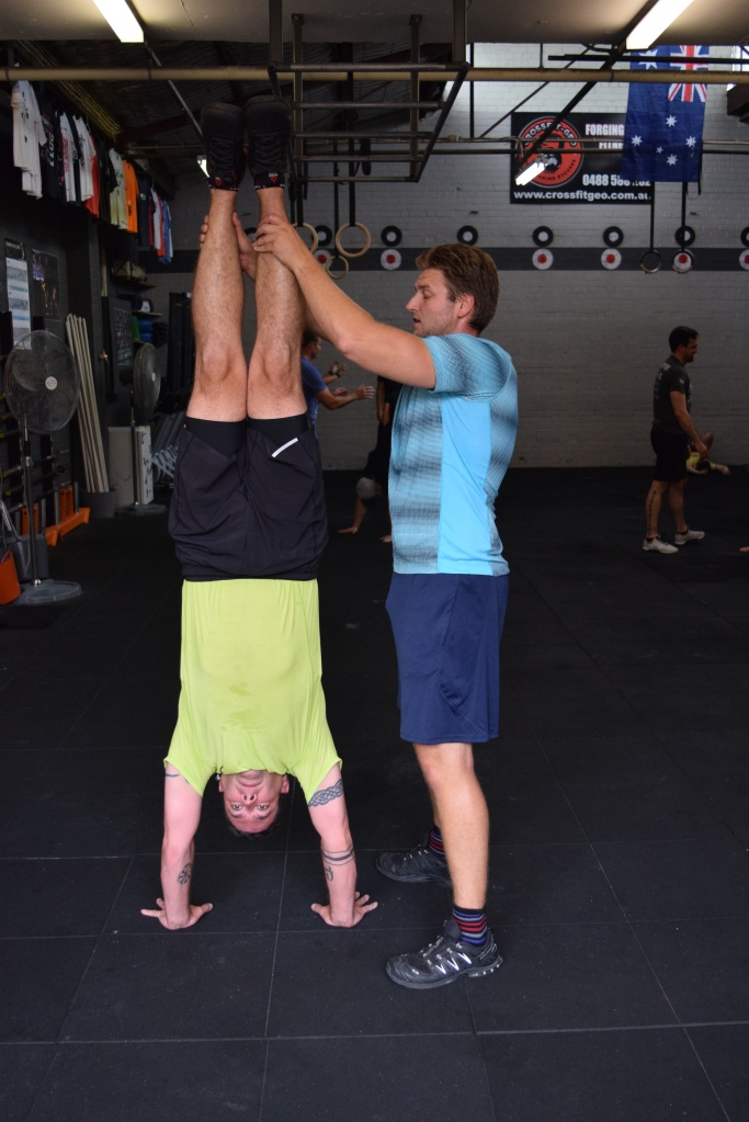 Jamie (upside down) and Kirill work on handstand progressions.